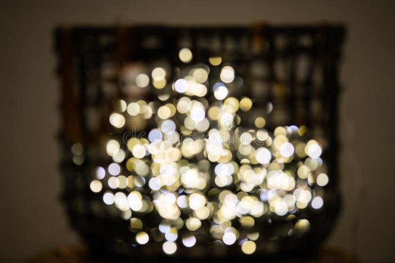 Dekorativt f?rgade felika ljus som gjordes suddig med bokeh, p? sk?rm i en korg arkivfoton