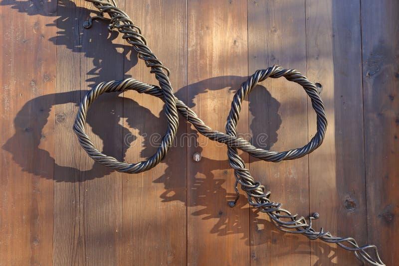 Dekorativt handtag av vridna metalltrådar på en trädörr arkivfoton