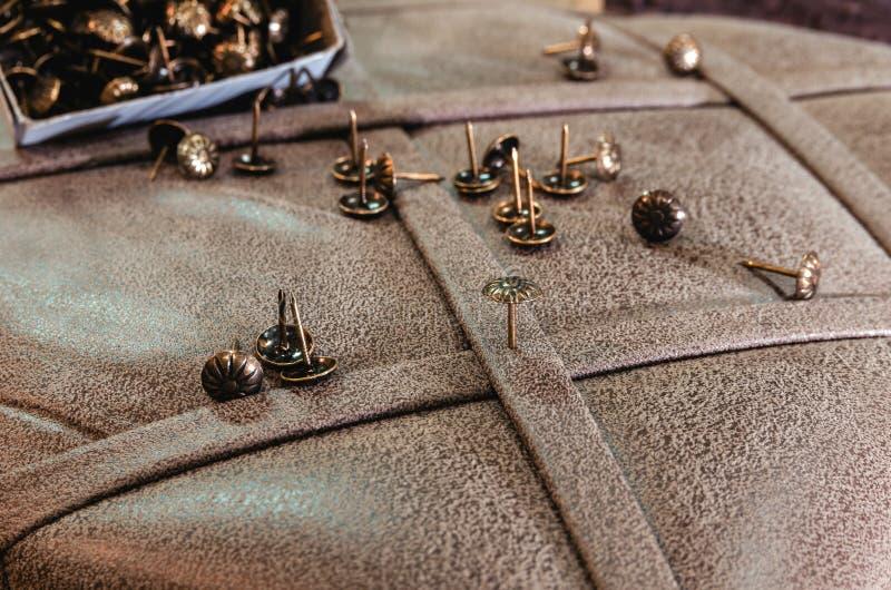 Dekorativt möblemang spikar på bakgrunden av tygstoppning arkivfoto