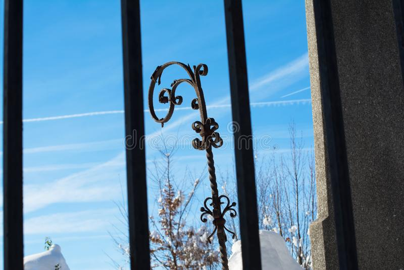 Dekorativt objekt för smidesjärn som igenom ses staketet för metallstång arkivfoto