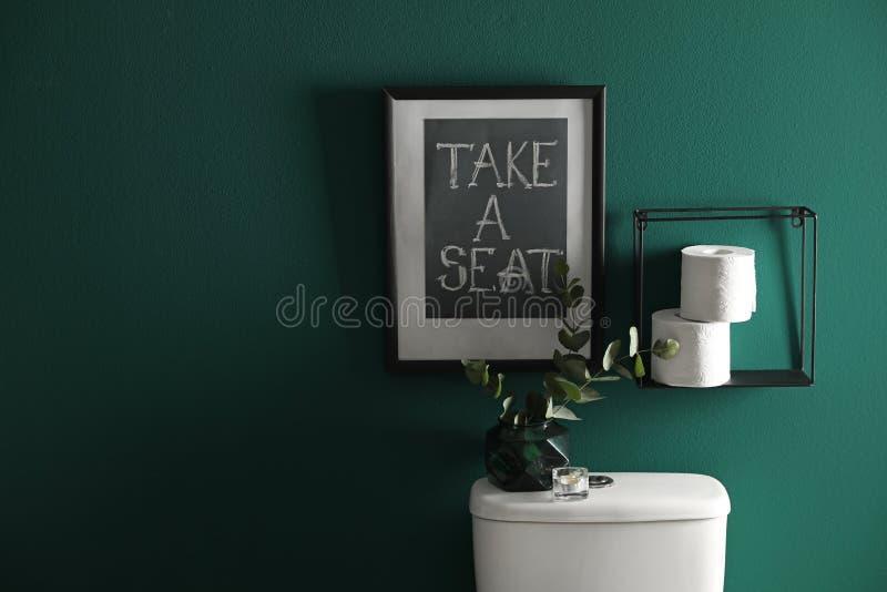 Dekorbeståndsdelar, pappers- rullar och toalettbunke nära den gröna väggen, utrymme för text Badrum I royaltyfri fotografi