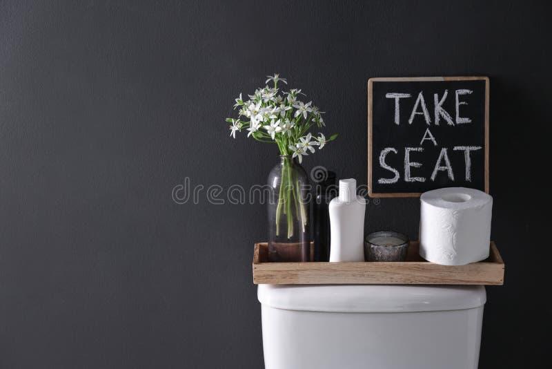 Dekorelemente, Notwendigkeiten und Toilettenschüssel nahe schwarzer Wand, Raum für Text Badezimmer stockfoto