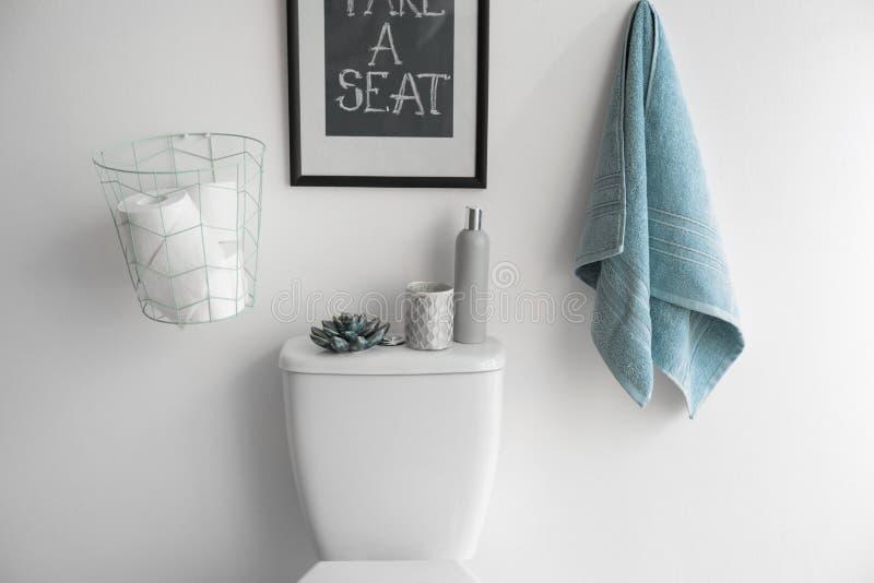 Dekorelemente, Notwendigkeiten und Toilettenschüssel nahe weißer Wand Badezimmer stockbild