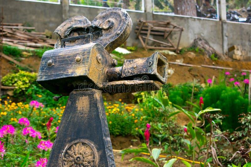 Dekoren för skulptur för den Rusty Black Old Broken Video kamerastenen förlade i en blommaträdgård arkivfoto