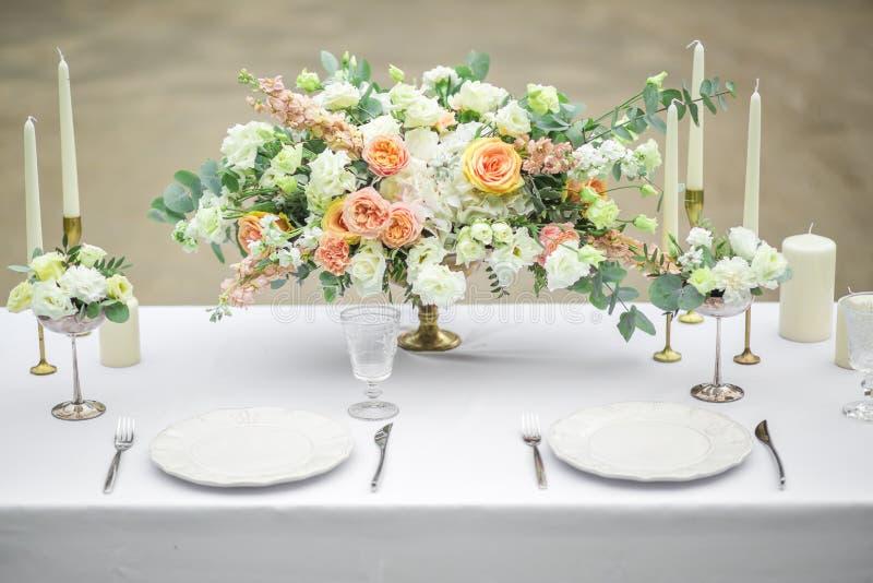Dekorerad brölloptabell för två med härlig blommasammansättning av blommor, exponeringsglas för vin och plattor, utomhus- som är  arkivbild