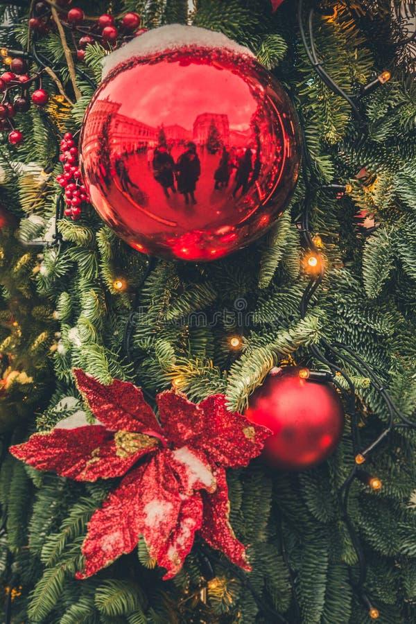 Dekorerad julgran med röda bollar, girland Utomhus- mässa Xmas-kort och modell close upp Vinter royaltyfri fotografi