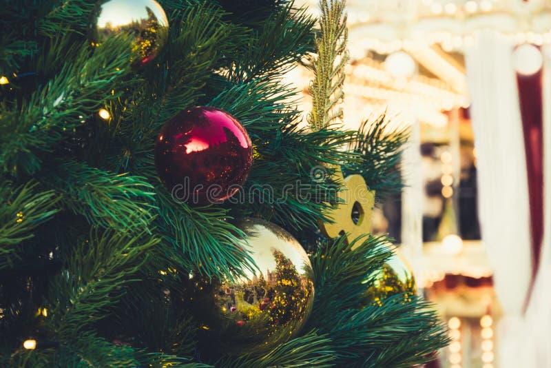 Dekorerad julgran med röda bollar och girlanden Utomhus- mässa Xmas-karusell close upp Vinter arkivfoto