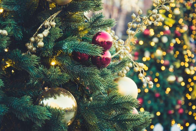 Dekorerad julgran med röda bollar och girlanden Utomhus- mässa Xmas-kort och modell close upp Vinter royaltyfri fotografi