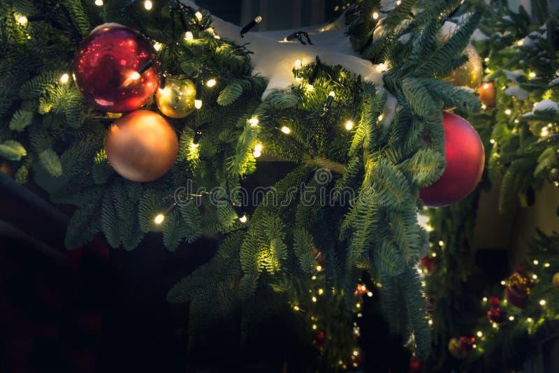 Dekorerad julgran med röda guld- bollar, girland Utomhus- mässa Xmas-kort och modell close upp Vinter royaltyfria bilder