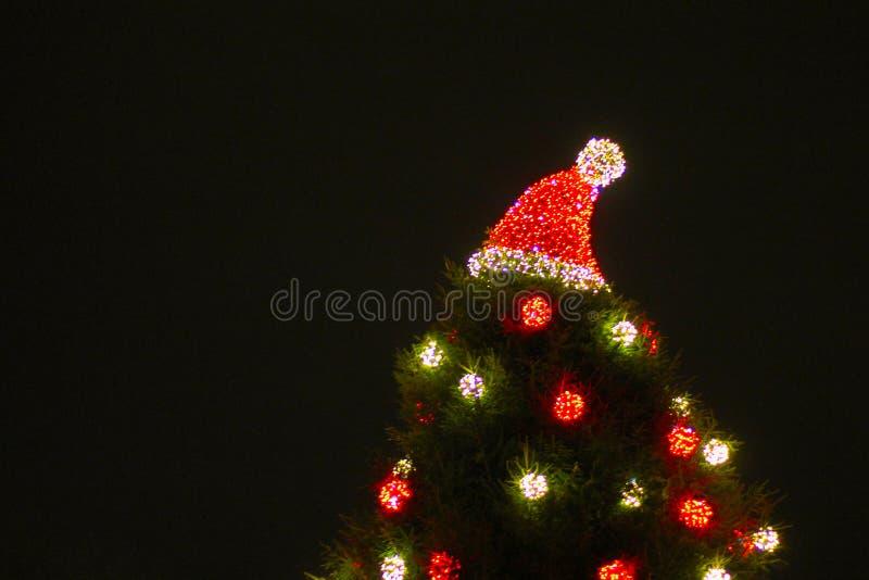 Dekorerad julgran som är utomhus- med ljus och jultomtenhatten royaltyfri bild