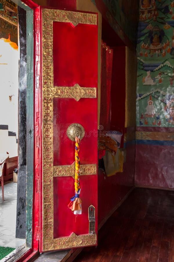 Dekorerad röd tempeldörr på den Thiksay kloster nära Leh, Indien royaltyfri bild