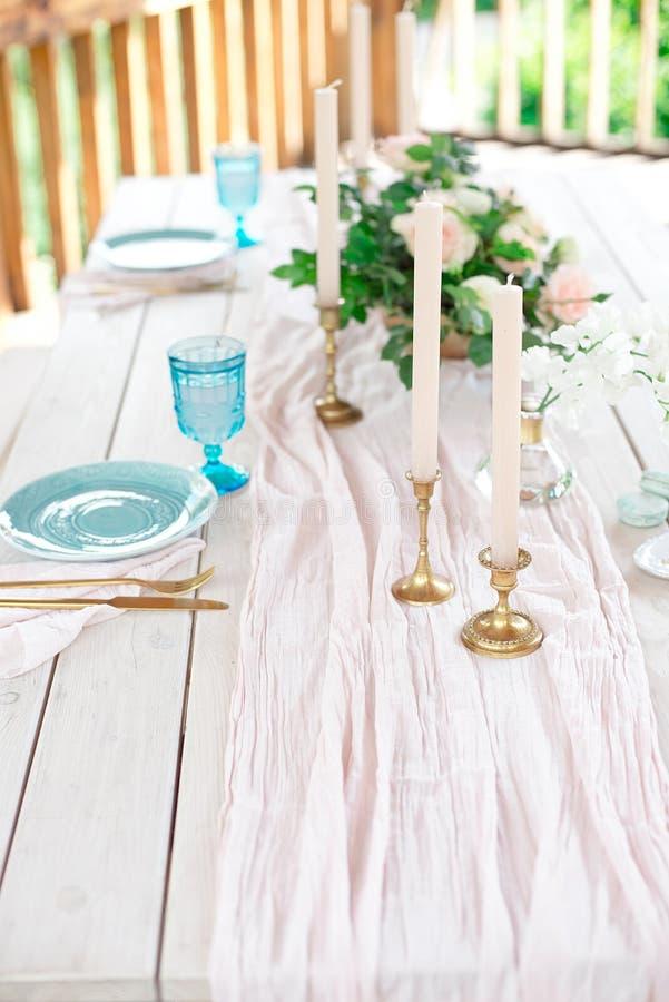 Dekorerad tabell för matställen för person två, med plattakniven, gaffeln, ost, vin, vinexponeringsglas och blommor i en kopparva royaltyfri bild