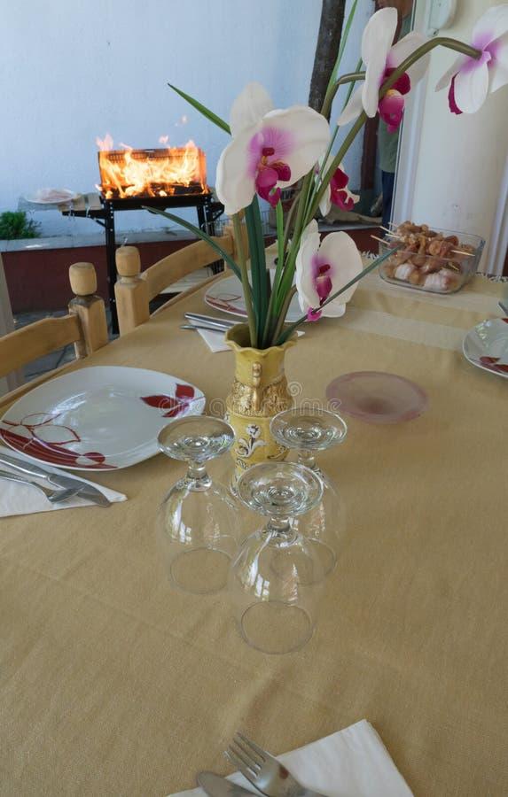 Dekorerad tabell i tr?dg?rden Begrepp för Dishwaredekormatställe Besegrar koppar för klart och rent vatten Grillfest i sommartid  royaltyfri foto