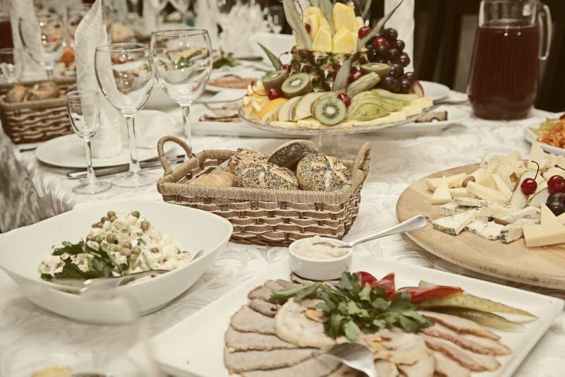Dekorerad tabell med mellanmål, frukter, sallader royaltyfri foto