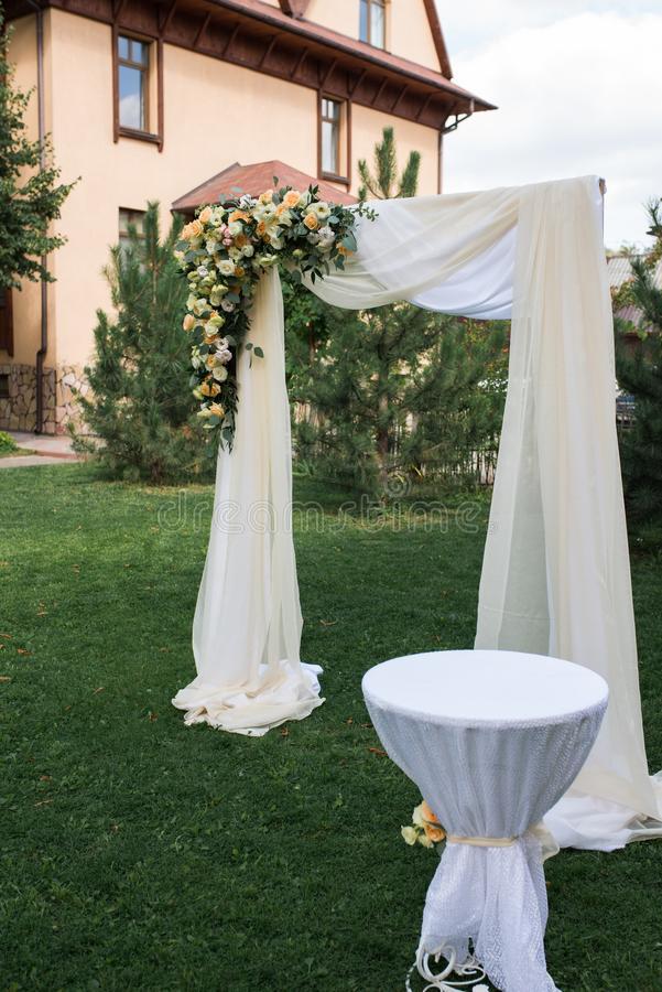 Dekorerade dekorerat område för öppen luft för bröllopceremonin med en träbåge med nya blommor och beige material Härligt gifta s arkivfoto