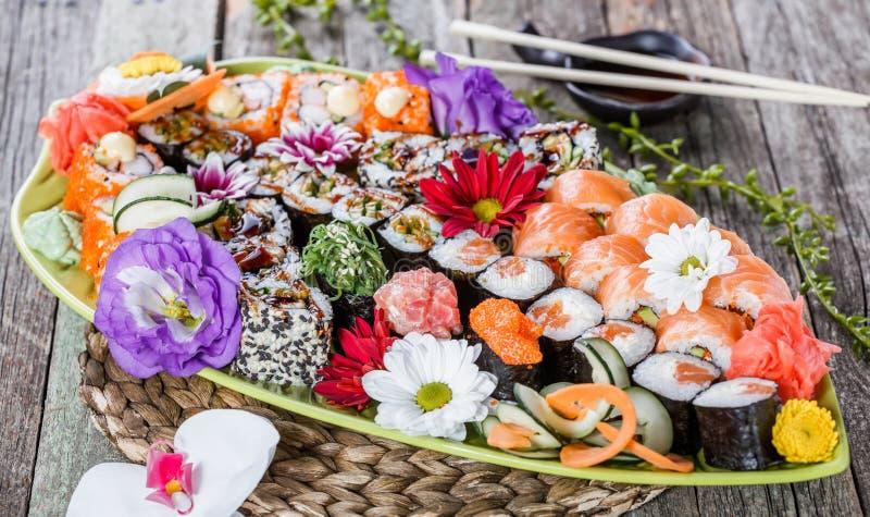 Dekorerade den fastställda nigirien för sushi och sushirullar med blommor på bambubakgrund Japansk kokkonst royaltyfri bild