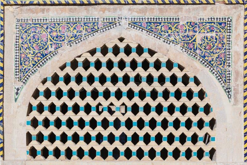 Dekorerade det härlig gammal tegelsten latticed fönstret med målningmosaiken, Iran arkivfoto