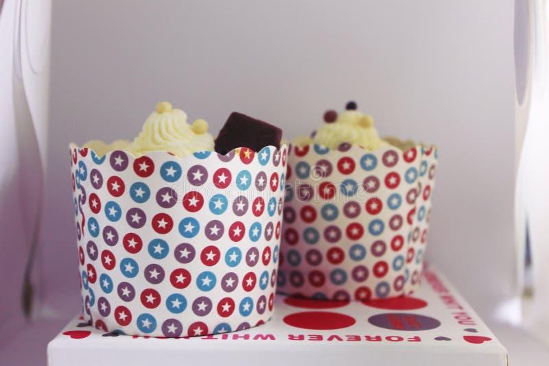 Dekorerade födelsedagmuffin på en ställning i en studio royaltyfri foto