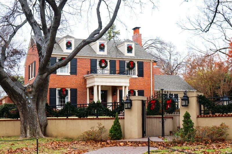Dekorerade huset för röd tegelsten för två berättelse i exklusiv lövrik bostads- neghborhood med den järnstaketet och porten beau arkivbild