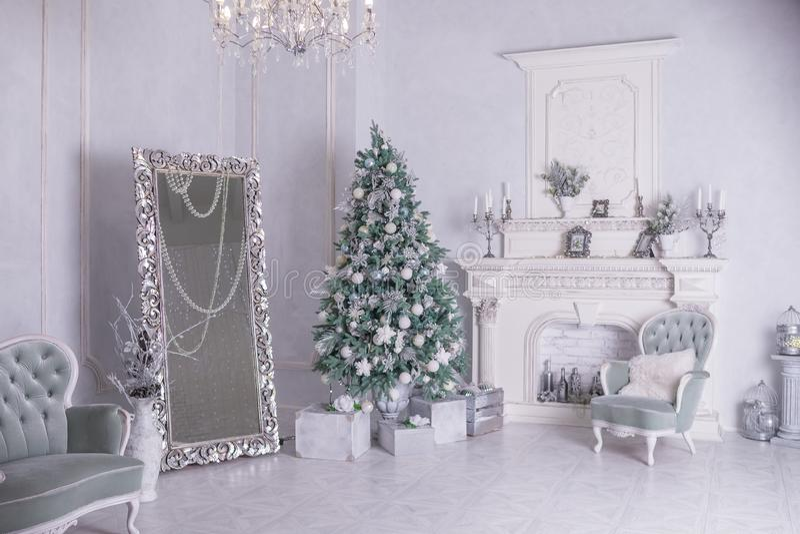 Dekorerade julgran- och gåvaaskar i vardagsrum stor vit vardagsrum med ett tappningmöblemang och ett stort arkivbilder