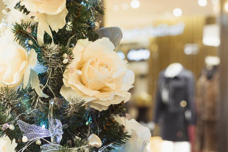 Dekorerade lyxiga pastellfärgade blommor för julgran på suddig shopwindow i galleriainre extra bakgrundsformatxmas arkivbild