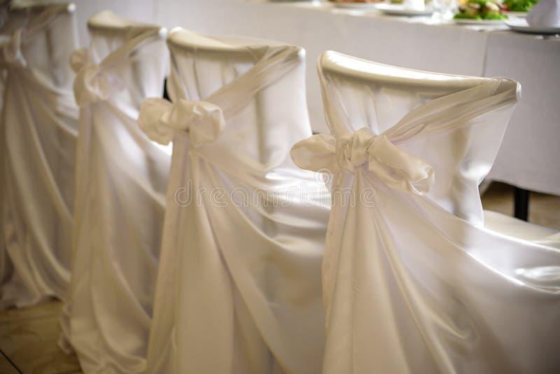 Dekorerade stolar med svart tyg och stora rosa satängpilbågar Siden- pilbåge som binds på baksida av stol i parti på restaurangen royaltyfri foto