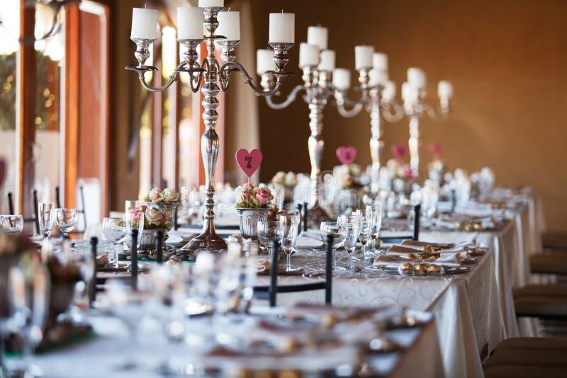 Dekorerade tabeller med kandelaber på bröllopmottagandet som är selektivt royaltyfri bild