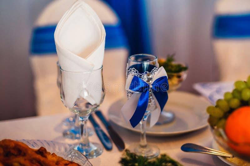 Dekorerade vinexponeringsglas för bröllop på tabellen i restaurang arkivbilder