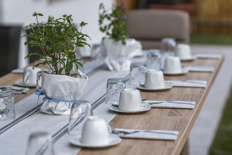 Dekorerat arbeta i trädgården tabellen med kaffekoppar royaltyfri foto