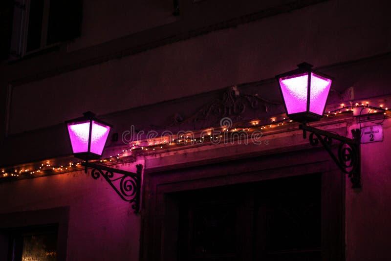 Dekorerat hus med julljus och två violetta lampor i natten royaltyfria bilder