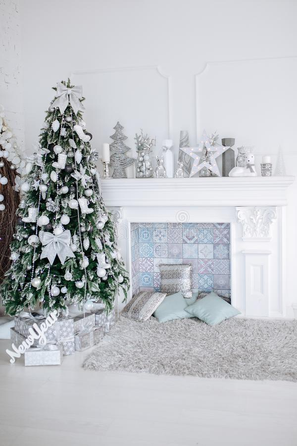 Dekorerat vitt inre rum för jul och för nytt år med gåvor och trädet och spisen för nytt år fotografering för bildbyråer