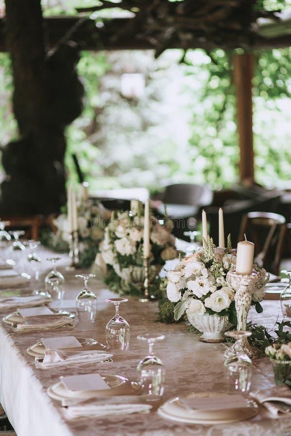 Dekorujący elegancki ślubu stół dla gościa restauracji z kwiecistymi białymi bukietami, candlesticks i bielu tablecloth szkłami,  obraz stock