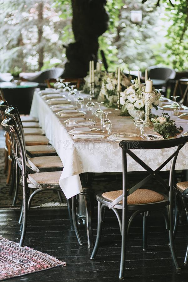 Dekorujący elegancki ślubu stół dla gościa restauracji z kwiecistymi białymi bukietami, candlesticks i bielu tablecloth szkłami,  zdjęcia royalty free
