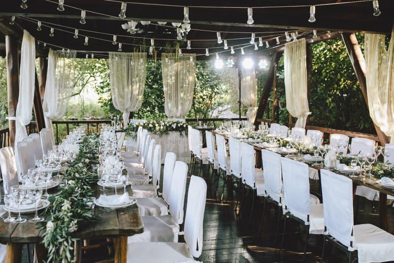 Dekorujący elegancki drewniany ślubu stół dla bankieta plenerowego w ogrodowym gazebo z lampą, w stylu wieśniaka z eukaliptusem i obrazy stock