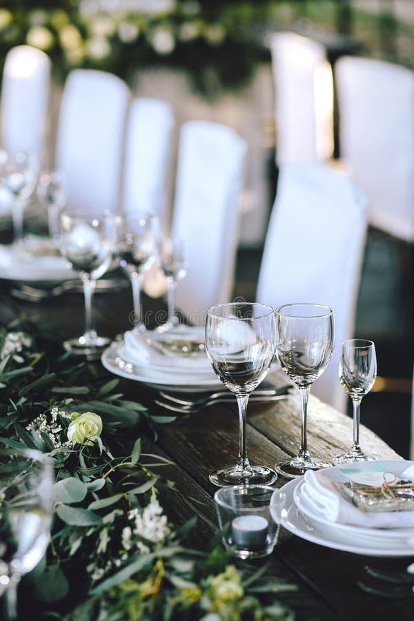 Dekorujący elegancki drewniany ślubu stół w wieśniaka stylu z eukaliptusem, kwiaty, porcelana talerze i szkła, obrazy stock