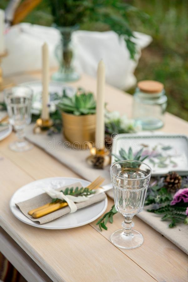Dekorujący elegancki drewniany stół w wieśniaka stylu z eukaliptusem, kwiaty, porcelana talerze, szkła, pieluchy i cutlery, zdjęcie stock