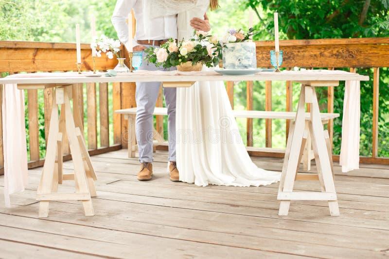 Dekorujący stół dla gościa restauracji dla dwa osoby z talerza nożem, rozwidleniem, serem, winem, win szkłami i kwiatami w grosza zdjęcia stock