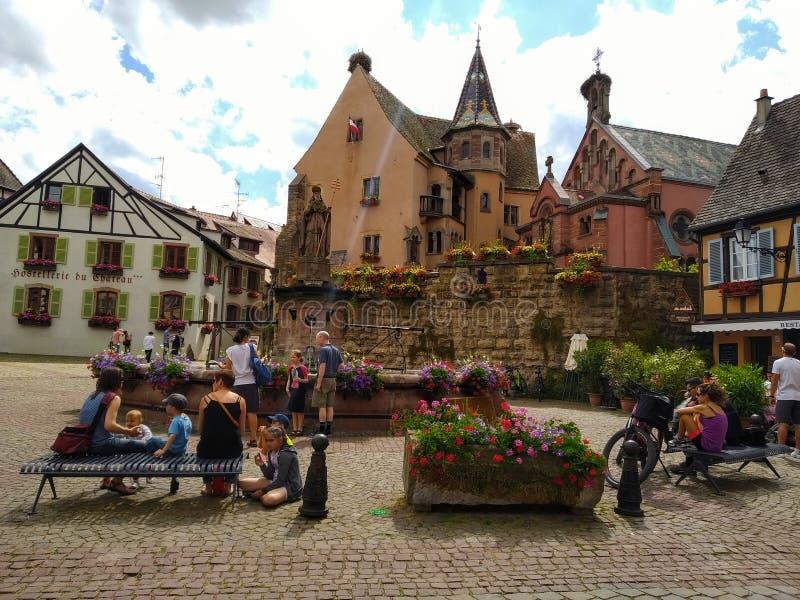 Dekoruję z kwiat fontanną w głównym placu Eguisheim otaczał typowymi domami Alsace, Francja zdjęcie royalty free