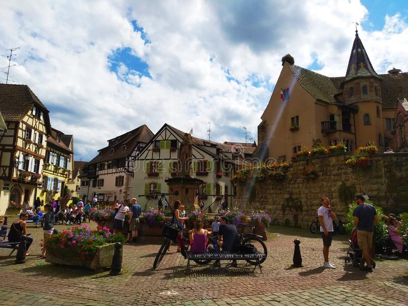 Dekoruję z kwiat fontanną w głównym placu Eguisheim otaczał typowymi domami Alsace, Francja obraz stock
