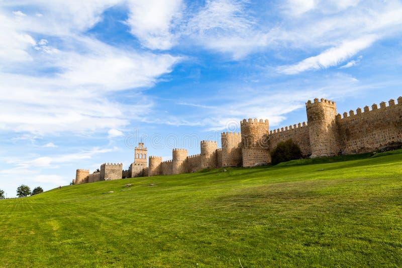 包围阿维拉、西班牙和绿色草坪城市的中世纪城市墙壁的看法在佩亚达del卡门前面 图库摄影