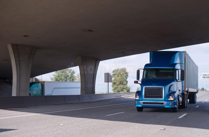 Del aparejo del azul camión grande semi que va debajo del puente fotos de archivo