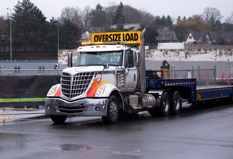 Del aparejo camión grande potente elegante semi con trai descender de la cama plana imagenes de archivo