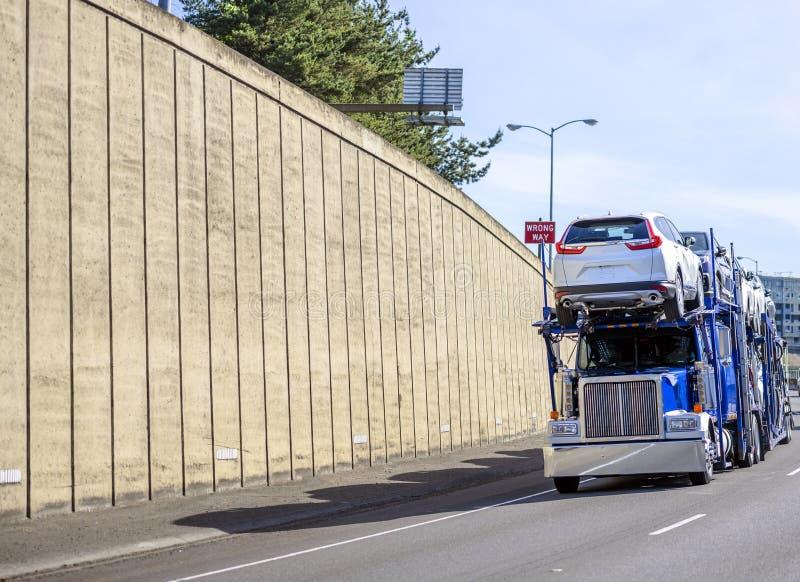 Del aparejo del coche del transportista camión grande azul semi que transporta los coches en semi el remolque que corre en el cam foto de archivo libre de regalías