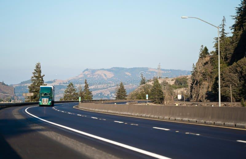 Del aparejo del verde camión grande semi que gira la carretera con curvas con m magnífico imágenes de archivo libres de regalías