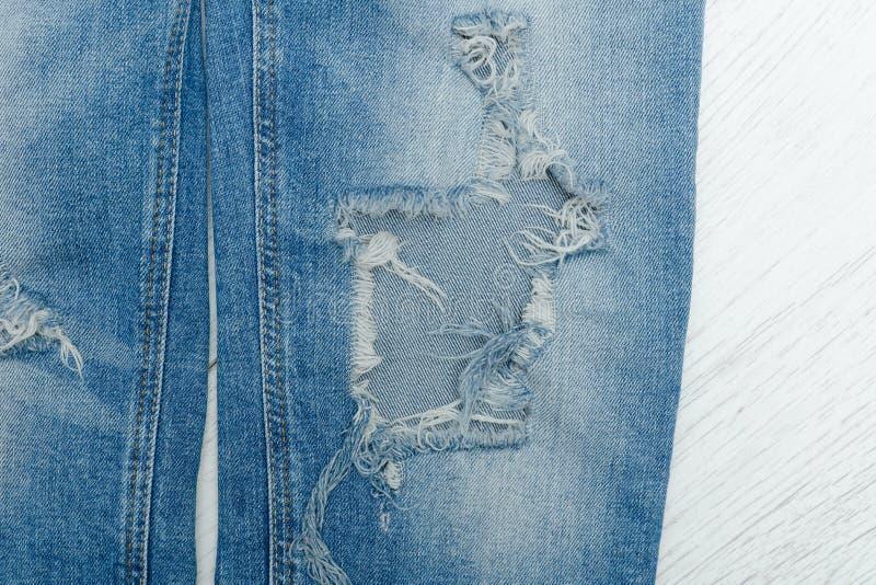 Del av blått riven sönder jeans Detaljnärbild royaltyfri bild
