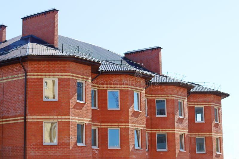 Del av bostads- byggnad för röd tegelsten med fönster och lampglas fotografering för bildbyråer