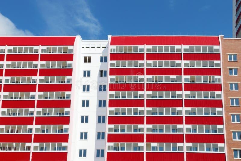 Del av bostads- byggnad med många röda loggior på soligt arkivfoto