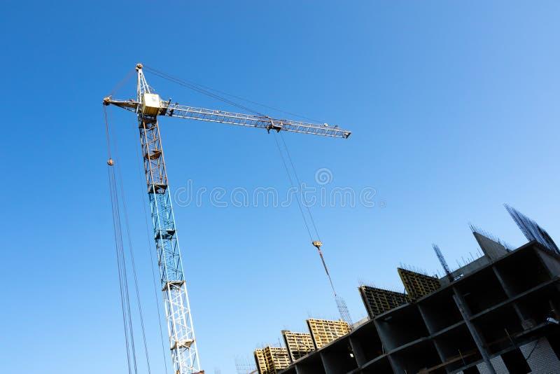 Del av byggnaden under konstruktion och tornkranen med det fällda ned repet på byggnaden arkivbilder