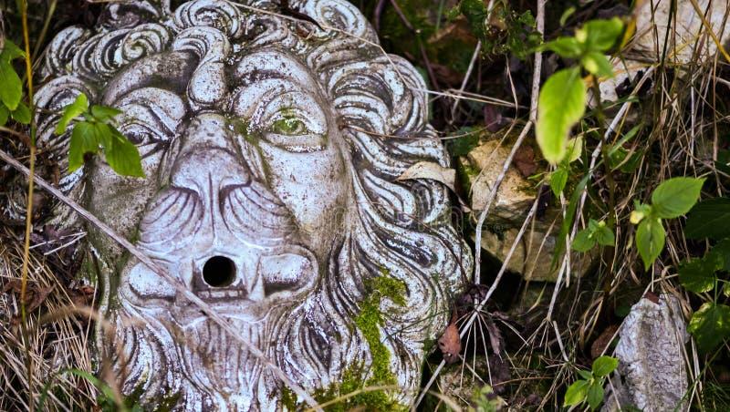 Del av den bevuxna trädgården Lejonstenmaskeringen, arbeta i trädgården skulptur royaltyfri foto