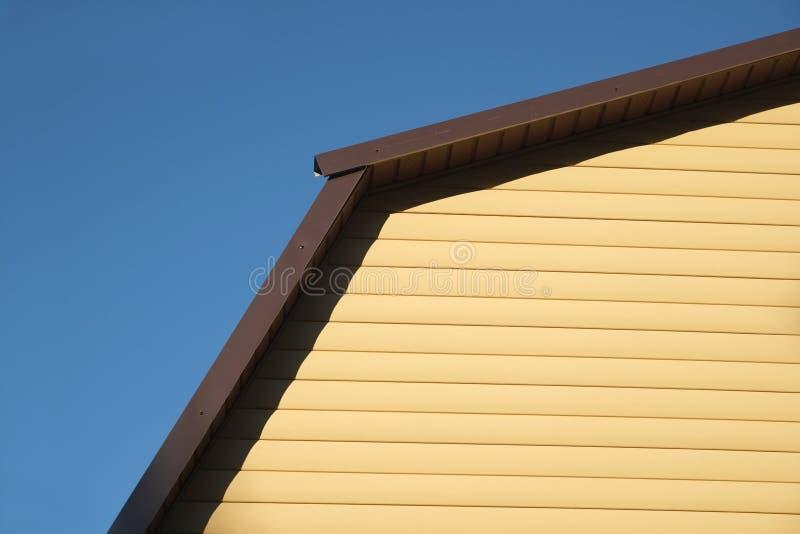 Del av den lantliga husväggen som täckas med främre sikt för gul siding och för brunt metalltak royaltyfri fotografi